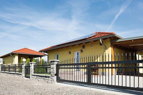 Zweiflügeltor konvex rund mit Dekorringen und Lanze in anthrazit, Modell Venezia, in grauer Steinmauer vor gelbem Haus