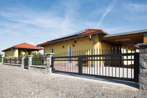 Kunstschmiedezaun Zweiflügeltor in anthrazit mit Dekorringen und Lanzen, Modell Venezia von GUARDI, vor gelbem Bungalow