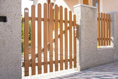 Gartentüre konvex rund in Holzoptik mit Rundkappen, Modell Merlin, vor rosa Haus