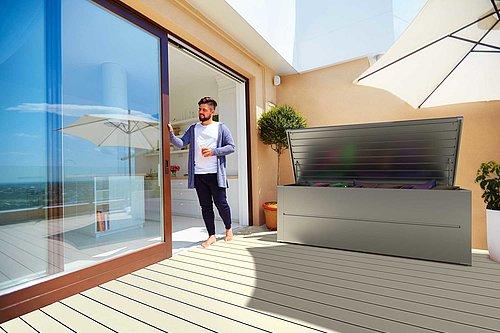 Moderne Gartenbox in silber metallic aus Stahl steht auf einem Balkon, ein Mann mit einer Tasse steht daneben
