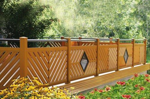 Balkongeländer in Holzoptik mit rundem Handlauf mit Muster, blühende Blumen stehen im Vordergrund