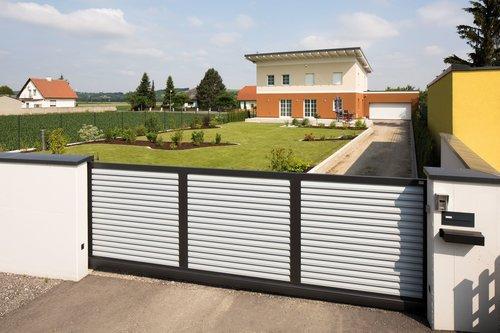 Blickdichtes Schiebetor aus Lamellen in weiß, Modell Trento von GUARDI, in Einfahrt von modernem Haus