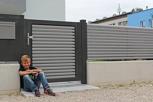Gartentüre aus Lamellen in grau mit Rahmenoptik in anthrazit, Modell Plissée, mit passendem Briefkasten, Kind sitzt vor Zaun am Boden