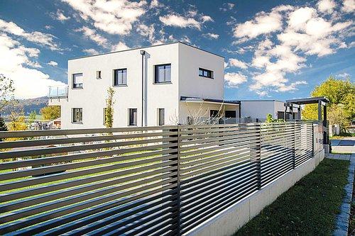 Lamellenzaun in anthrazit, Modell Linea von GUARDI, Gewinner-Zaun des Infinity Design Award, vor einem weißen, modernen Haus