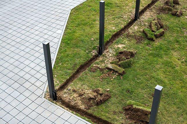 Ein Grundstück von oben fotografiert, auf dem Steher für den geplanten Zaun zu sehen sind