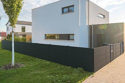 Blickdichter Lattenzaun in anthrazit mit passender Gehtür, Modell Vista von GUARDI, vor einem weißen, modernen Haus