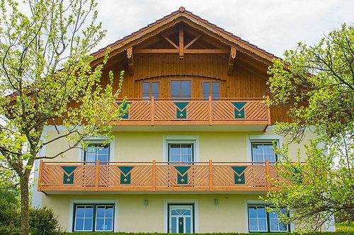 Balkongeländer vom Modell Gastein in Holzoptik aus Aluminium von Guardi, linke und rechts sind zwei grüne Bäume