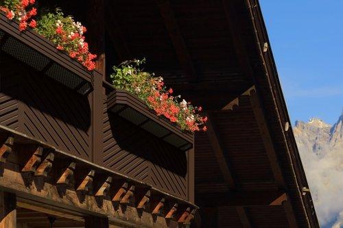 Balkongeländer von mit dem blickdichten Modell St. Anton in verschiedenen Farben mit Blumenkisten, im Hintergrund sind Berge zu sehen