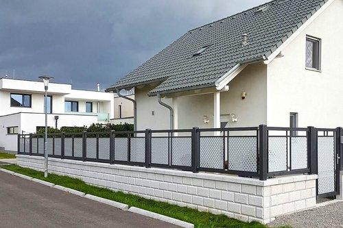 Dekorzaun in anthrazit mit grauer Lochblechfüllung, mit passender Gartentüre, Modell Loskana von GUARDI, vor weißem Einfamilienhaus