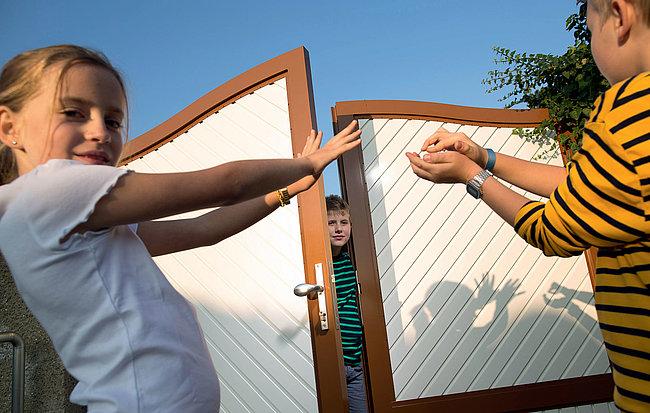 Drei Kinder spielen vor einem halb geöffneten, blickdichten Flügeltor aus Aluminium