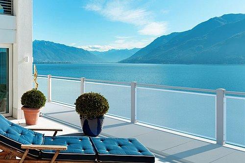 Balkongeländer vom Modell Loos in anthrazit als Sichtschutz ausgeführt, die Aussicht ist auf einen blauen See im Hintergrund gerichtet
