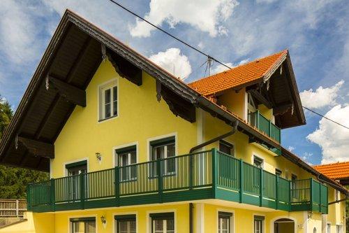 Alubalkon mit 3-fach-Stäben und Handlauf in grün, Modell Parma, auf gelbem Bauernhaus
