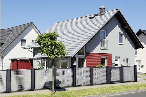 Architektonischer Lochblechzaun in grau mit schwarzen Stehern, mit passender Gehtür, Modell Loos von GUARDI, vor grauem Haus