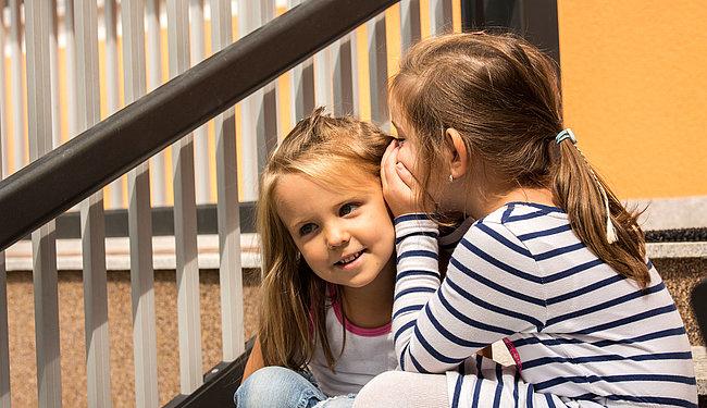 Zwei Mädchen sitzen auf einer Treppe vor einem Aluminiumzaun und flüstern sich gegenseitig etwas ins Ohr