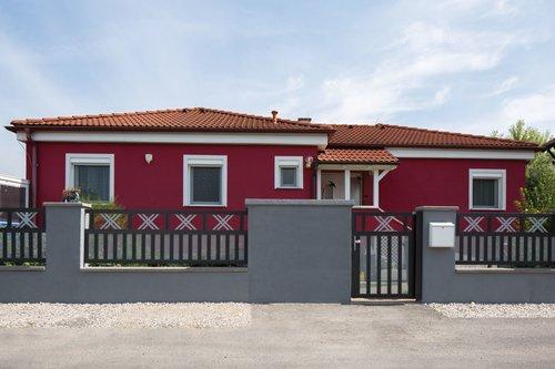 Breitstabzaun in anthrazit mit Kruezornament und Lochblechfüllung in grau, mit passender Gartentür, Modell Modena von GUARDI, vor rotem Bungalow