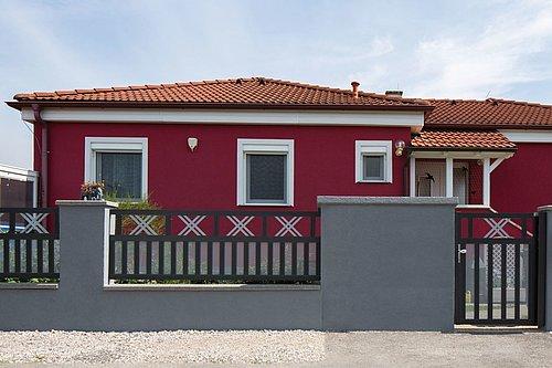 Breitstabzaun in anthrazit mit Kreuzornament und Lochblechfüllung in grau, mit passender Gartentüre, Modell Modena von GUARDI, vor rotem Bungalow