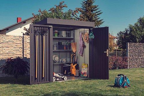 Eine moderne Gartenhütte aus Stahl in anthrazit steht geöffnet in einem Garten, darin sind viele Werkzeuge und Gartenutensilien zu sehen