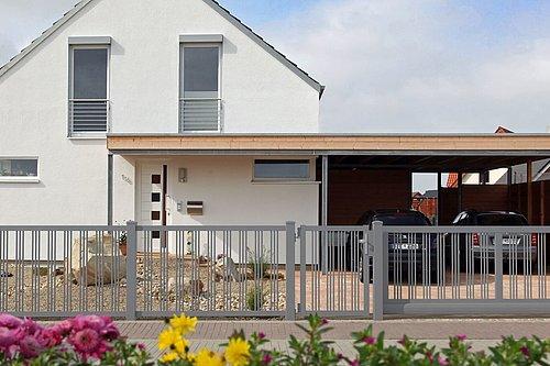 Schiebetor aus 3-fach-Rundstäben mit passender Gartentüre in grau, Modell Parma, vor weißem Haus mit Carport