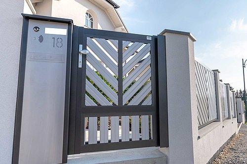 Gehtüre aus Aluminium in zweifärbiger Ausführung doppelt-diagonale V-Form mit integrierter Briefkastensäule