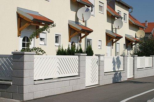 Aluminiumzaun in weiß, Modell Umbria von Guardi mit Gartentür, doppelt-diagonal A-Form, dahinter ein weißes Reihenhaus
