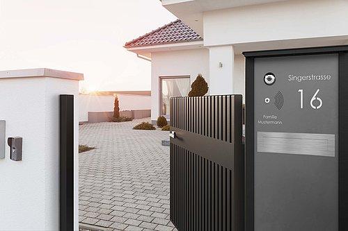 Gartentür in anthrazit mit passender Briefkastensäule designed von Studio F.A. Porsche, Modell Epos, vor einem weißen, modernen Haus