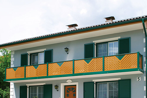 Balkongeländer aus Aluminium vom Modell St. Anton in Holzoptik und grün, die Festerläden des Hauses sind ebenfalls in grün