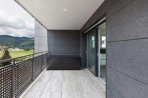 Gartenbox in Größe M von Guardi in anthrazit steht auf einer Terrasse in der hinteren Ecke, links ist ein Balkongeländer mit Lochausschnitten