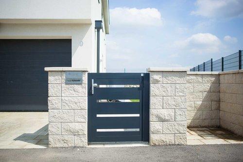Gartentür aus Latten in anthrazit, Modell Triest, integriert in Steinmauer, Garage im Hintergrund