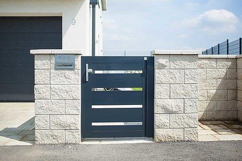 Gehtür aus Latten in anthrazit, Modell Triest, integriert in Steinmauer, Garage im Hintergrund