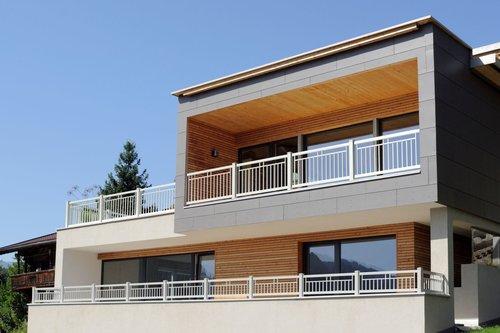 Balkon aus Einzelstäben in weiß, Modell Toskana, auf einem modernen, grauen Haus mit Holzelementen