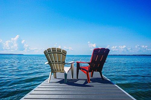Terrassenboden in grauer Optik als Steg am Meer ausgeführt, darauf stehen zwei Sessel, im Hintergrund trifft der Horizont auf das Meer