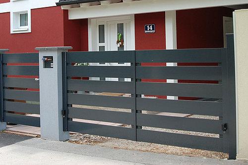 Moderner Gartenzaun mit Flügeltor und Gehtüre mit Querlatten aus Aluminium begrenzt ein Grundstück vor einem roten Haus
