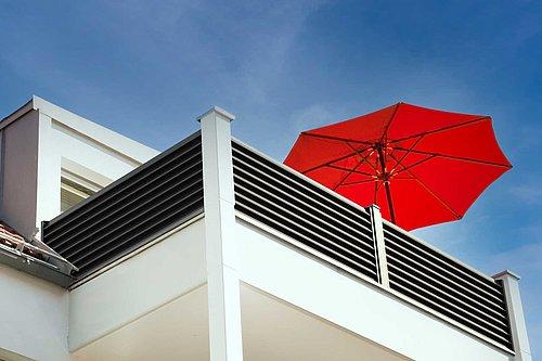 Balkongeländer aus Aluminium vom Modell Trento, ein großer roter Sonnenschirm ragt über den Balkon hinaus