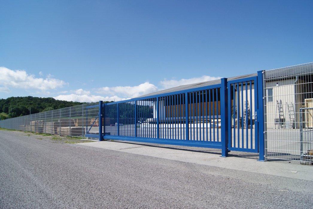 Blaues Industrieschiebetor aus Aluminium von Guardi grenzt ein Firmengelände ab.