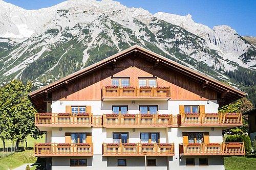 Balkongeländer vom Modell Gastein in anthrazit, montiert ist der Balkon auf einem modernen Holzhaus, links und rechts stehen Laubbäume