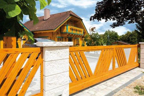 Sonderbau Schiebetor in Holzoptik, dazu Betonsäulen und im Hintergrund steht ein Holzhaus