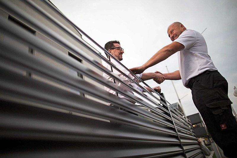 GUARDI Mitarbeiter reicht einem Kunden über einen Aluzaun hinweg die Hand